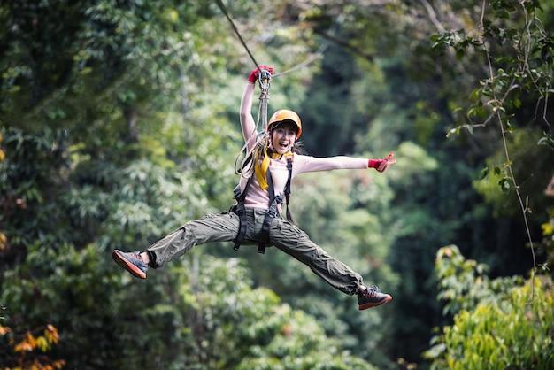 Turista della donna che porta abbigliamento casuale sulla linea dello zip o esperienza del baldacchino in foresta pluviale del laos, asia