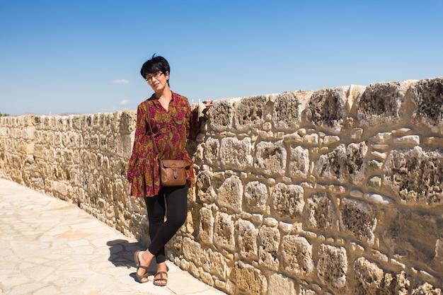 Turista della donna che posa vicino al castello medievale.