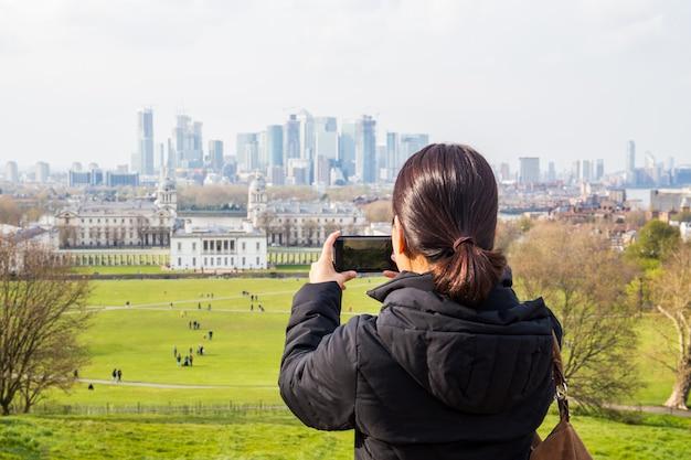 Turista della donna che prende le immagini nel parco con la città che bulding