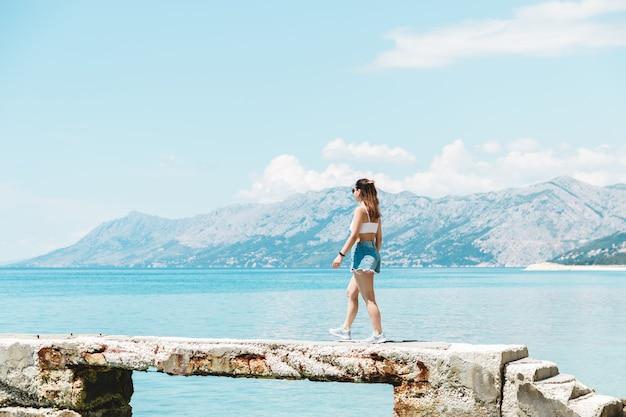 Turista della donna nella splendida posizione in viaggio dopo il blocco sentirsi libero godendo della vista della montagna del mare e dell'aria fresca