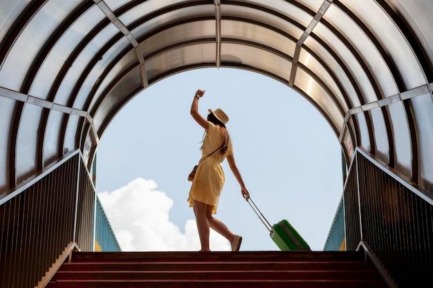 Turista della foto a figura intera con bagaglio verde