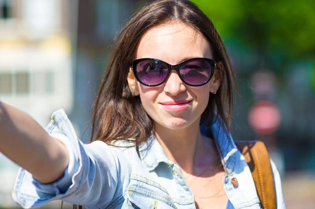 Turista della giovane donna che prende la foto del selfie dell'autoritratto sul viaggio dell'europa nella città di amsterdam