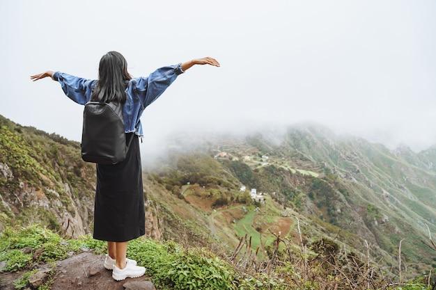 Turista della giovane donna con lo zaino che si rilassa sulla cima di una montagna e che gode della vista della valle