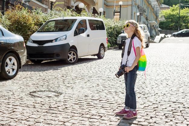 Turista della ragazza del bambino felice con la macchina fotografica