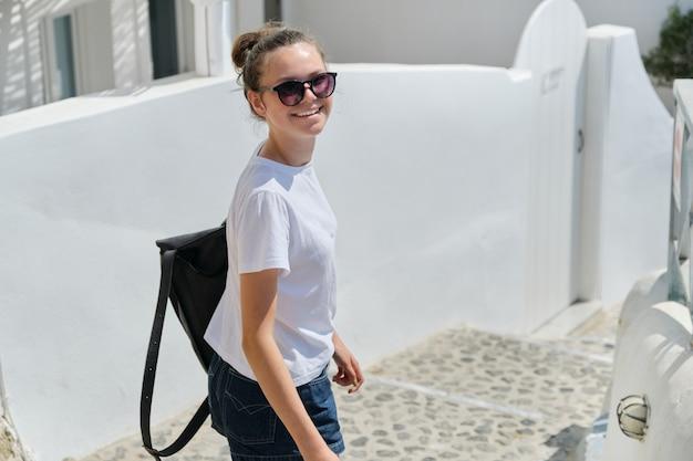 Turista della ragazza nella città soleggiata di estate con architettura mediterranea bianca