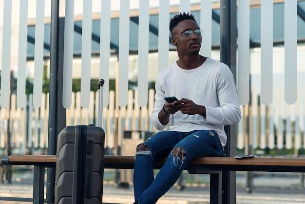Turista di giovane uomo barbuto con zaino e smartphone