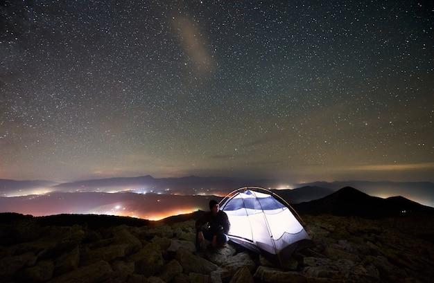 Turista di notte in campeggio in cima alla montagna sotto il cielo stellato