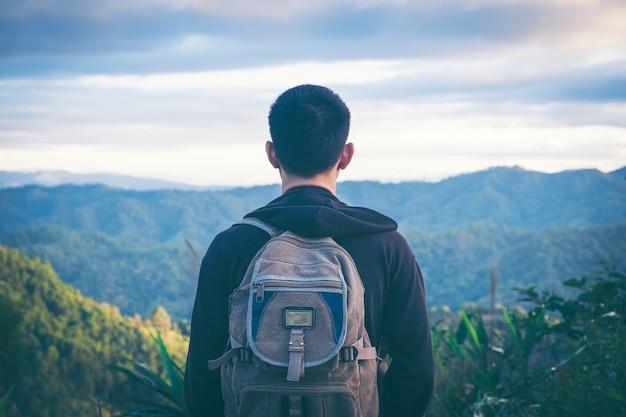 Turista di tipo uomo bello in piedi da solo dal paesaggio forestale di montagna durante le sue vacanze estive con la sua vista posteriore zaino