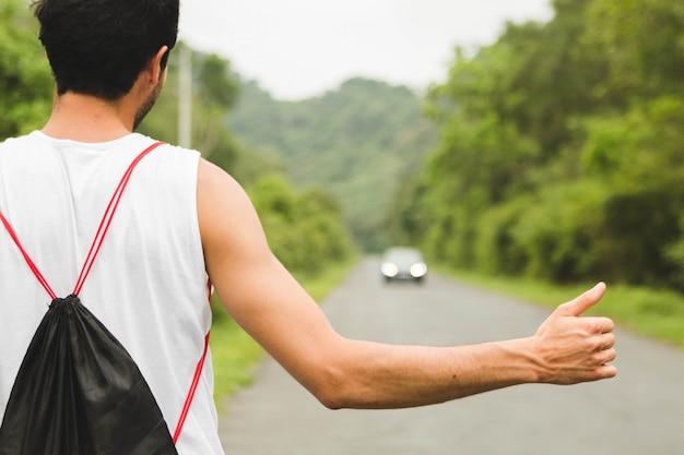 Turista di viaggiatore con zaino e sacco a pelo che fa auto-stop sulla strada della montagna nel vietnam