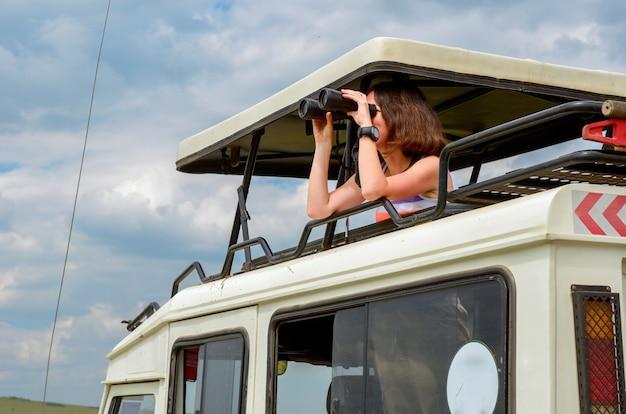 Turista donna in safari in africa, viaggio in kenya, osservare la fauna selvatica nella savana con il binocolo