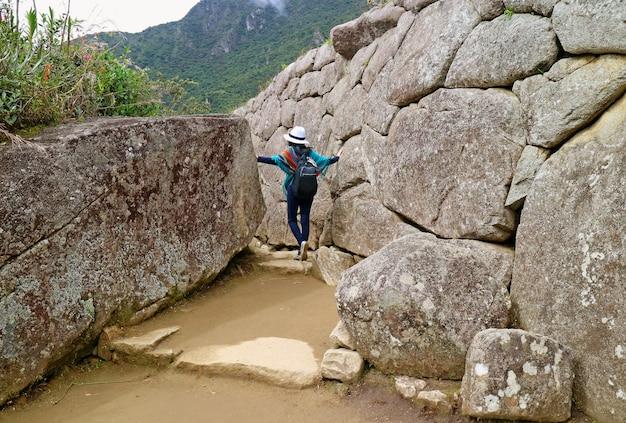Turista femminile che esplora le rovine antiche di inca della cittadella di machu picchu nella regione di cusco, perù