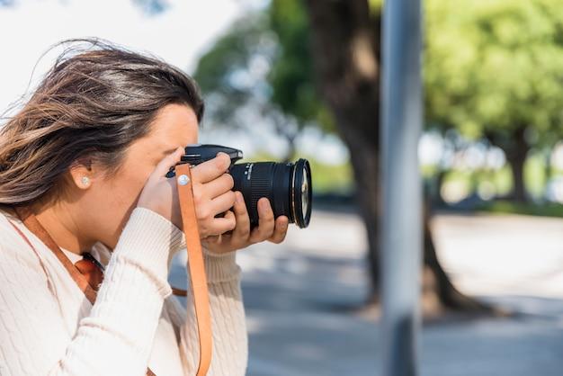 Turista femminile che fotografa dalla macchina fotografica professionale all'aperto