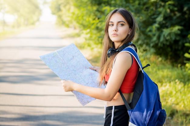 Turista femminile con una mappa e uno zaino pesante guardando indietro