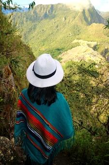 Turista femminile nell'ammirare la vista della cittadella di machu picchu dalla montagna di huayna picchu, cusco, urubamba, perù.