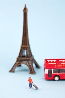 Turista in miniatura di torre eiffel e donne su sfondo blu