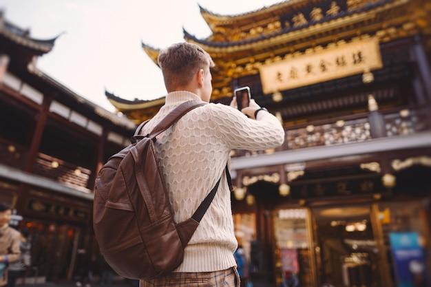 Turista maschio che prende le foto di una pagoda al mercato di yuyuan a shanghai