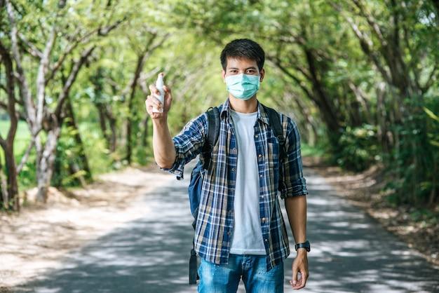 Turista maschio con una borsa a tracolla e in piedi con una bottiglia di alcol in mano.