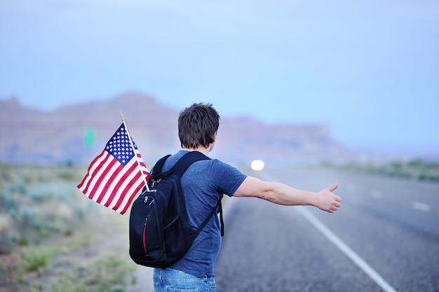 Turista maschio di medio evo con la bandiera americana in zaino autostop lungo una strada desolata