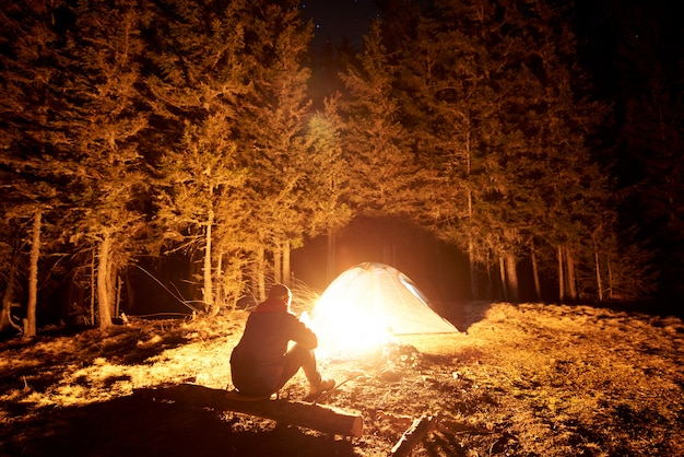 Turista maschio riposarsi nel suo accampamento di notte vicino al fuoco e tenda sotto il bellissimo cielo notturno pieno di stelle e la luna e godersi la scena notturna in montagna