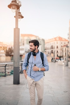 Turista maschio sorridente che cammina sulla pavimentazione