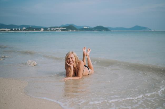 Turista senior anziano emozionante sorridente felice della donna che gioca in acqua e che nuota nelle grandi onde sulla spiaggia del mare dell'oceano. in viaggio lungo l'asia, concetto di stile di vita attivo.