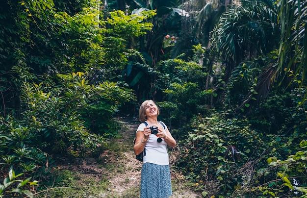 Turista senior della donna di viaggiatore con zaino e sacco a pelo di viaggio asiatico senior anziano che cammina godendo prendendo le foto nella giungla di sanya. in viaggio lungo l'asia, concetto di stile di vita attivo. alla scoperta di hainan, in cina