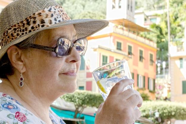 Turista senior femminile che beve acqua di rinfresco a portofino piazzetta