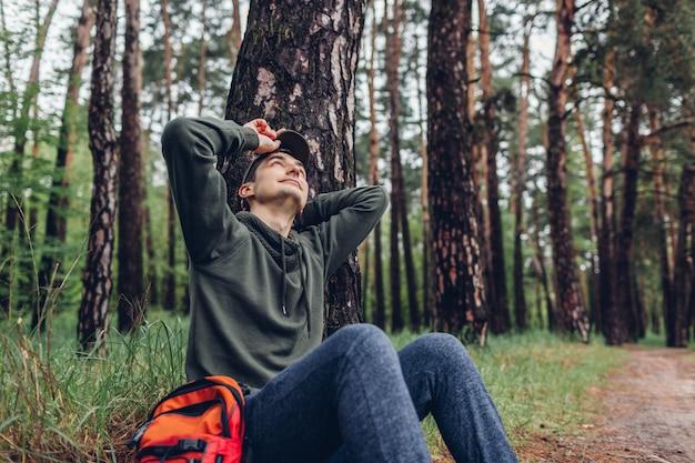 Turista stanco dell'uomo che dorme nella foresta di primavera. il viaggiatore si fermò per riposarsi. concetto di campeggio, viaggi e sport