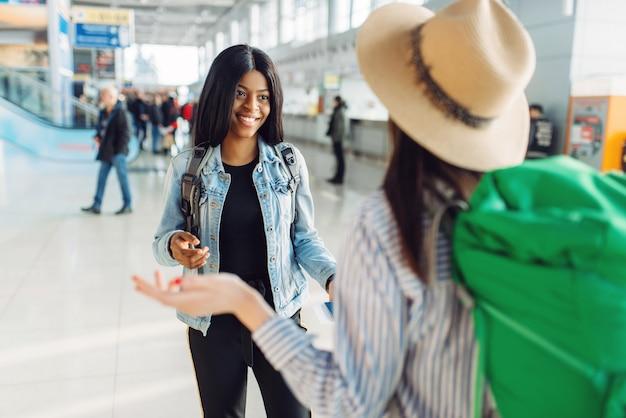 Turiste con borse in aeroporto internazionale