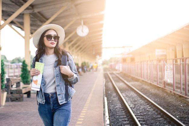 Turiste con in mano una borsa di occhiali neri, un cappello e in mano una cartina alla stazione ferroviaria.