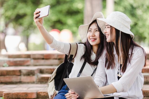 Turisti asiatici delle giovani donne che prendono un selfie in città