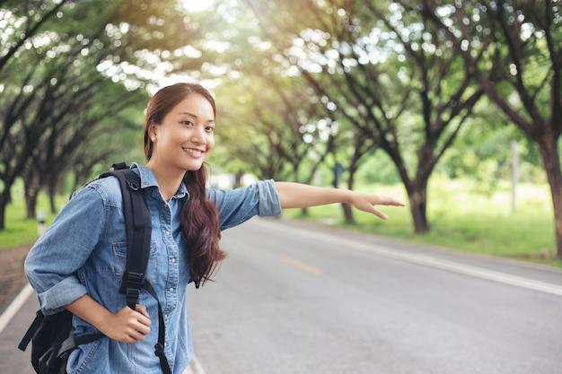 Turisti asiatici donne e saccopelisti in attesa di auto e