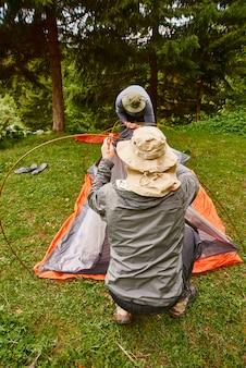 Turisti che installano una tenda nel campeggio. l'uomo in possesso di una tenda durante l'installazione di una tenda nella foresta