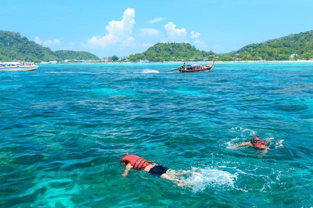 Turisti che nuotano e si immergono nel mare delle andamane a phi phi isole una delle più belle dell'isola in thailandia