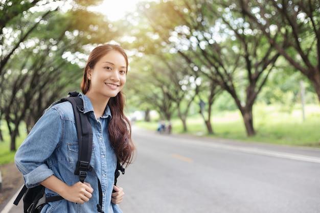 Turisti e backpackers asiatici delle donne che aspettano automobile