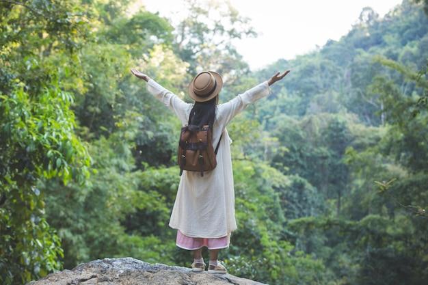 Turisti femminili allargano le braccia e tengono le ali, sorridendo allegramente.