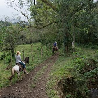 Turisti femminili che godono a cavallo nella foresta, finca el cisne, honduras