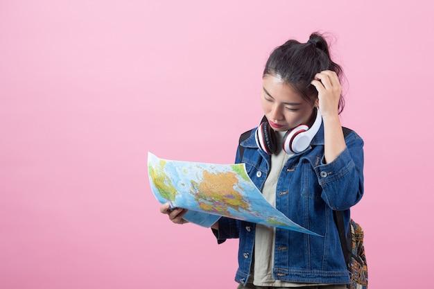 Turisti femminili in studio su uno sfondo rosa.