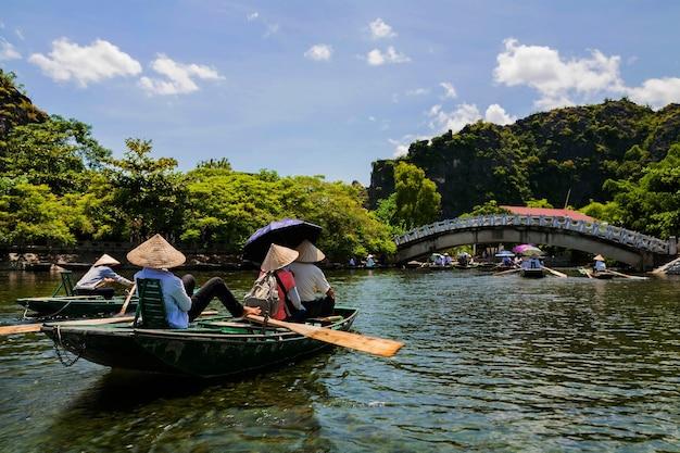 Turisti in barche di legno per viaggiare tam coc
