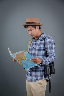 Turisti maschi che trasportano zaini portando una mappa di sfondo grigio.