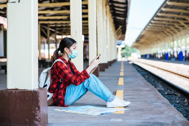 Turisti seduti e guardando i telefoni sul sentiero accanto alla ferrovia.