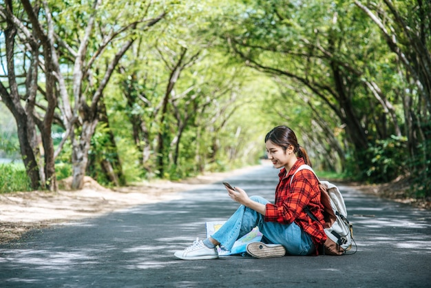 Turisti seduti e guardare i telefoni sulla strada.