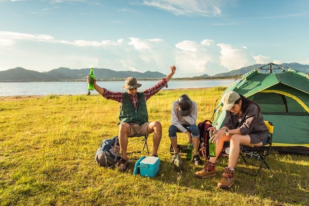 Turisti ubriachi che fanno festa mentre si accampano e fanno un picnic nel campo del prato