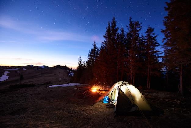 Turistico campeggio vicino alla foresta di sera.