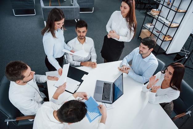 Tutti sono di buon umore. vista superiore degli impiegati nell'usura classica che si siede vicino alla tavola facendo uso del computer portatile e dei documenti