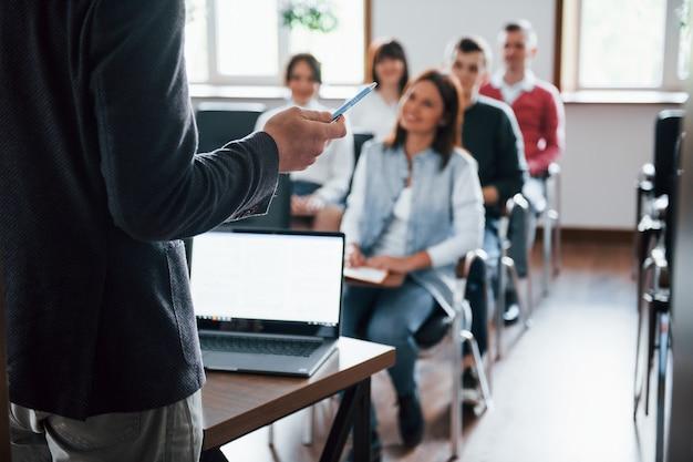 Tutti sorridono e ascoltano. gruppo di persone alla conferenza di lavoro in aula moderna durante il giorno