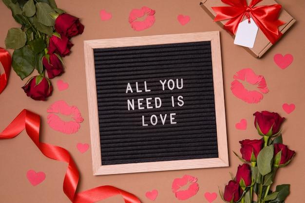 Tutto ciò di cui hai bisogno è amore - segno di lettera di feltro di san valentino con rose rosse, calori e baci.