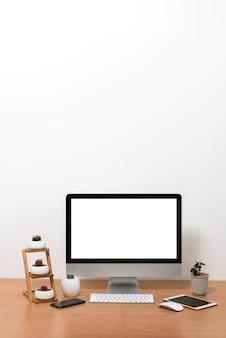 Tutto in un computer, mouse, tastiera, smartphone, tablet, vasi di cactus e vaso per piante