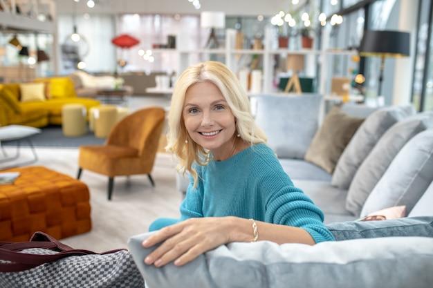 Tutto per gli interni. bella donna seduta sul divano, mettendo la mano in un braccialetto su un cuscino in una grande stanza tutto per l'interno, sorridente.