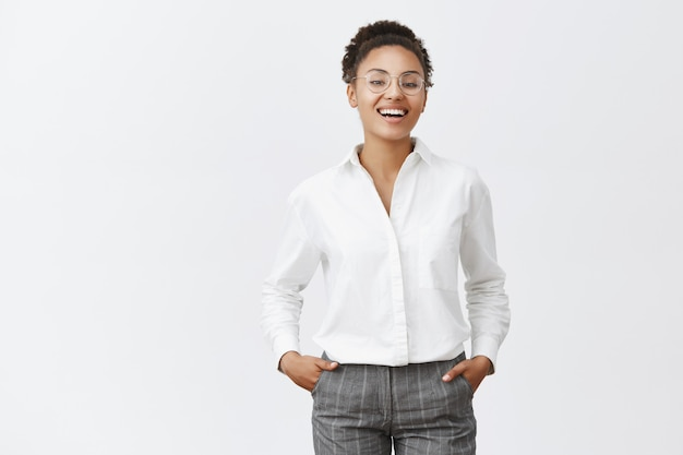 Tutto sotto controllo. bella femmina africana con occhiali, camicia e pantaloni, tenendo le mani in tasca, sorridendo e ridendo con espressione sicura, trionfante, vedendo ottimi risultati di lavoro